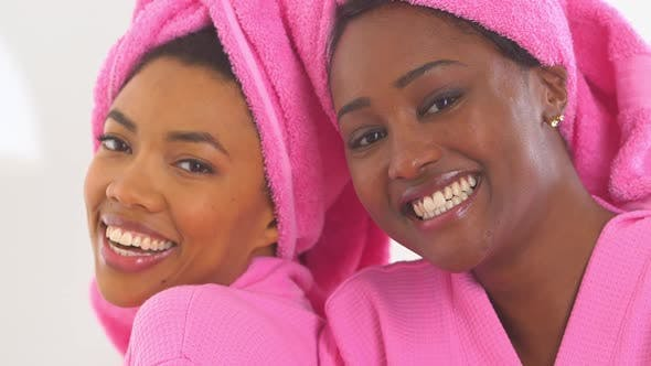 Thumbnail for Two African American friends in spa smiling with heads together