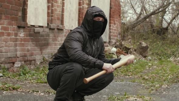 Maskierter Bandit mit Baseballschläger am verlassenen Platz