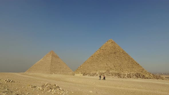 Tourists walking in front of Giza pyramids