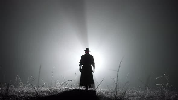 Silhouette of Plague Doctor Man in Long Mantle Costume and Hat Is Walking Ahead Through Smoke To