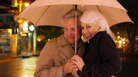 Thumbnail for Happy elderly couple standing in the rain with an umbrella