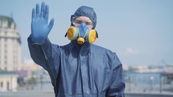 Thumbnail for Portrait of Confident Man in Chemical Suit Stretching Hand in Protective Blue Glove To Camera