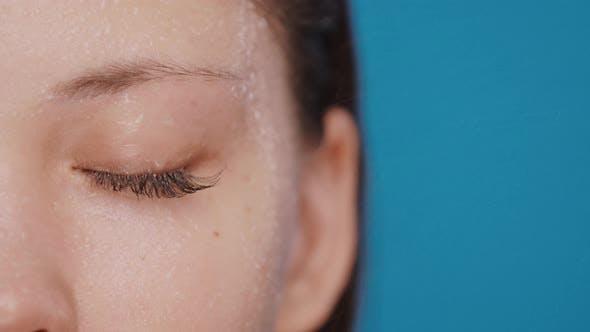 Thumbnail for Nahaufnahme der geschlossenen Frau Auge mit Wasserspritzern und Tropfen Isoliert auf Blau