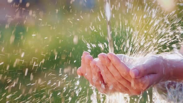 Thumbnail for Water Flows Into Open Human Palms. Splashes Effectively Fly Apart in the Sun