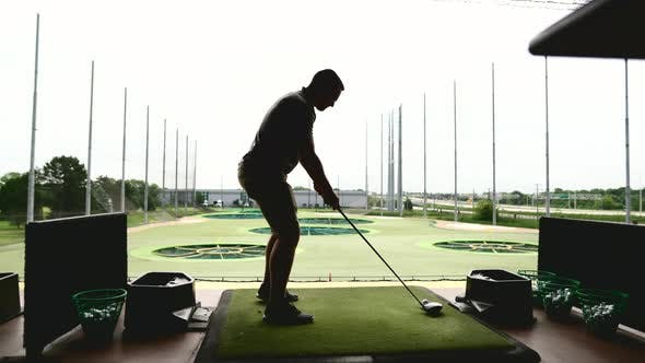 Thumbnail for Silhouette of a Man Playing Top Golf on a Playground with a Stick in His Hands on a Green Lawn