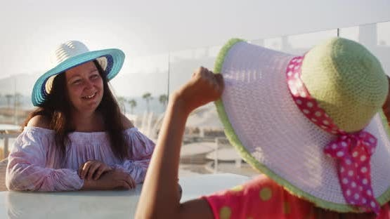 Smiling Woman in Summer Hat Talking with Girl Friend Sitting in Outdoor Cafe