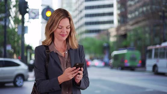 Thumbnail for Professional woman texting on smartphone outside on city street downtown