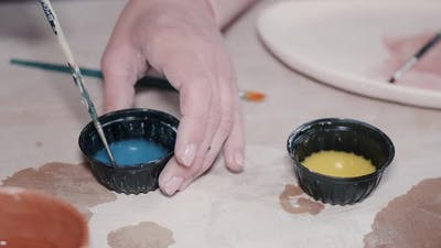 Craftsman Hands Painting a Clay