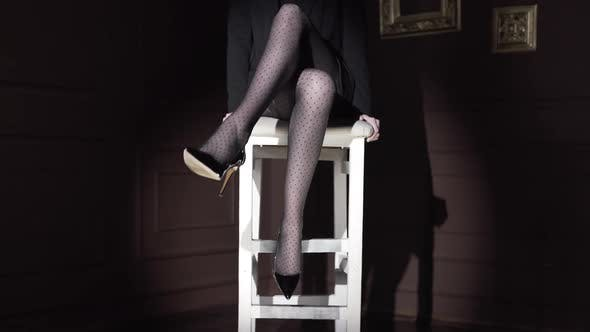 Thumbnail for Sexy Woman Sits on the High Chair in Polka Dot Tights and Shake Her Leg in the Dark, Long Sexy Woman