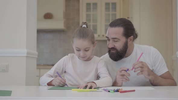 Thumbnail for Bearded Man and Little Girl Draw with Markers Sitting at the Table at Home