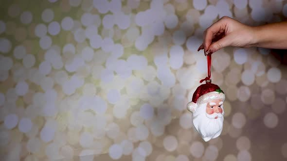 A woman's hand with gold glittery nails holding a Santa ornament with a glittery background