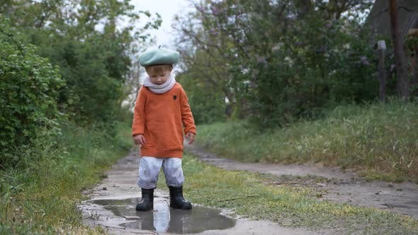 Thumbnail for Spring Break, Cute Male Child in Hat and Rubber Boots Have Fun Jumping in Dirty Puddle
