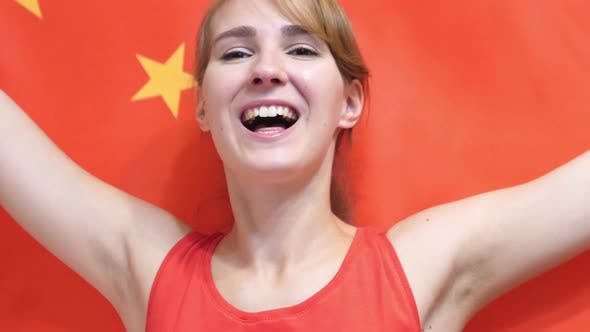 Chinese Young Woman Celebrating while Holding the Chinese Flag