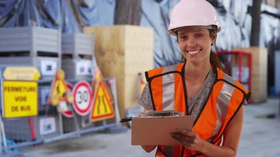 Thumbnail for Female construction worker in hardhat and vest smiling at camera on job site