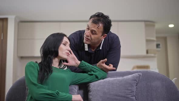 Medium Shot of Loving Middle Eastern Man Talking with Sad Caucasian Woman Supporting Spouse