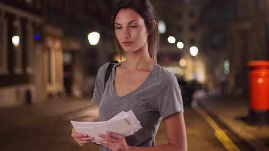 Thumbnail for Portrait of Caucasian woman holding stack of mail in city street at night