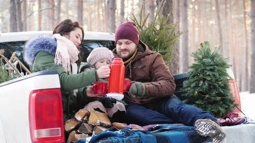 Happy Family of Three People Is Drinking Hot Tea From a Thermos, Sitting in the Back of a Car Near