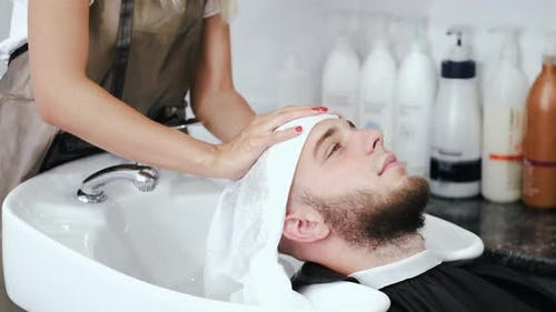 Stylist Wiping Client's Head with White Towel in Salon