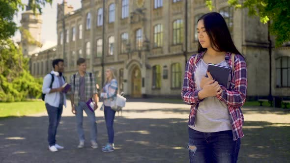 LOnely Biracial Girl Standing Alone, Upset About Mockery and Jokes of Classmates