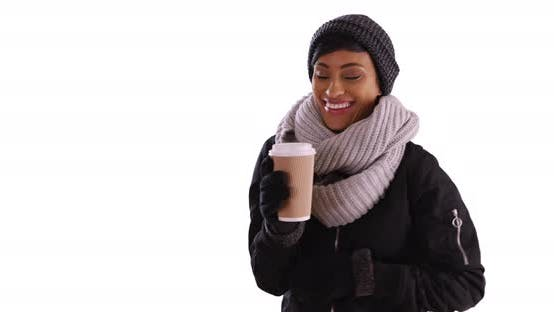 Thumbnail for Cute black woman in her 20s wrapped in scarf holding coffee cup in studio