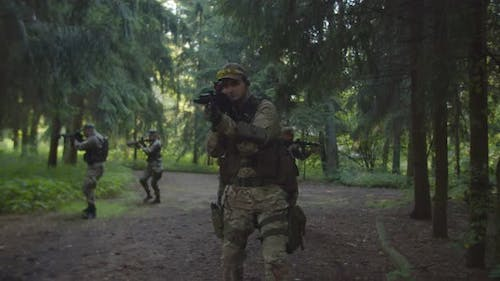Squad of Soldiers Moving Forward in Forest Rifles in Firing Position