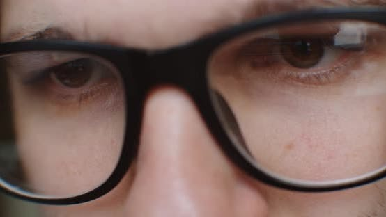Thumbnail for Man in Glasses Searching in Internet. Close-up. Eye Watching Display.