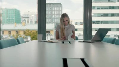 Young Business Woman in Conference Room with Papers
