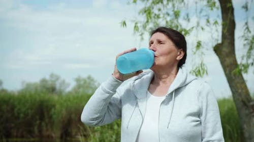 Lifestyle, Beautiful Elderly Woman Takes Care of Health Quenches Her Thirst Drinks Clean Cool Water