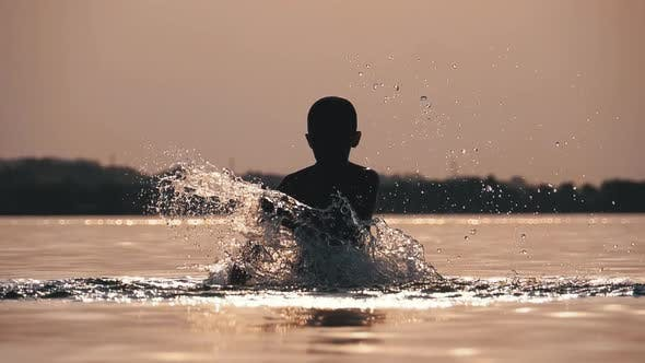Thumbnail for Silhouette of Happy Boy at Sunset Creating Splashes of Water with His Hands. Slow Motion