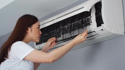 young woman removing air filter of the air conditioner for cleaning at home