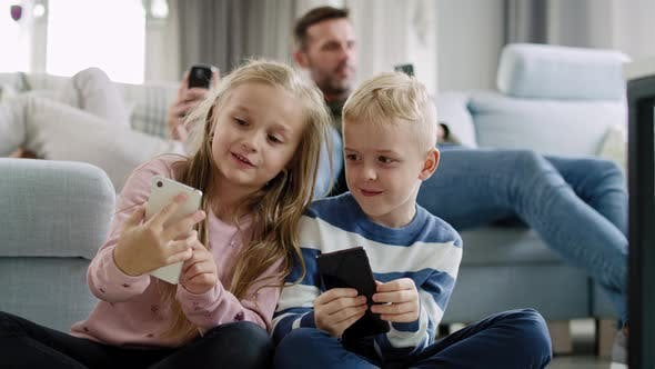 Thumbnail for Handheld view of children using mobile phone in living room