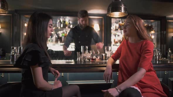 Thumbnail for Two Girlfriends Sitting Near Bar Counter Having Interesting Conversation