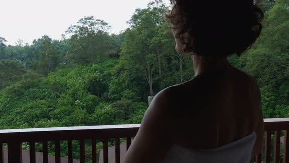 Back View of a Silhouette of a Woman Going on a Balcony After Morning Shower Holding White Mug of
