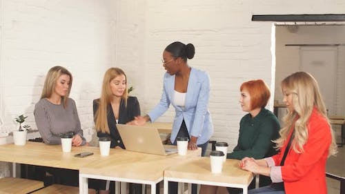 African Female Boss Telling Off Her Female Employees, Sitting in Meeting Room