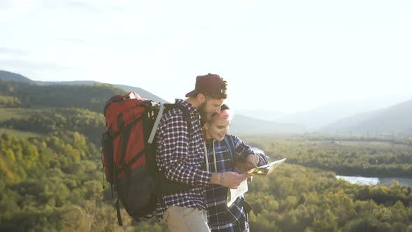 Thumbnail for Portrait Shot of Young Man and Woman with Map in the Mountains