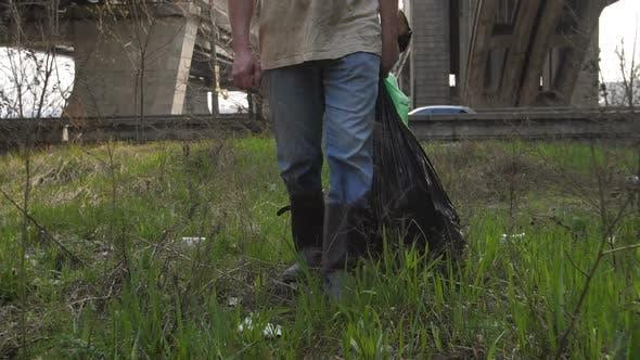 Legs of Man Walking with Trash Bags