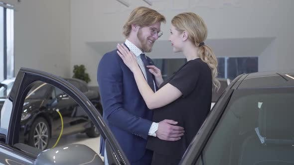Thumbnail for Happy Man and Woman Just Bought Car in Modern Motor Show. Couple Hugging Near Automobile