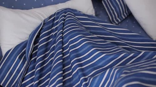 Portrait of a Happy Cute Funny Cheerful Little Child Boy in White Pajamas Wakes Up in Bed in the