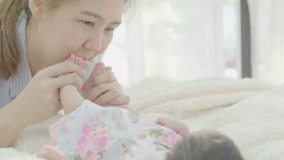Asian Mother playing with her adorable newborn baby.