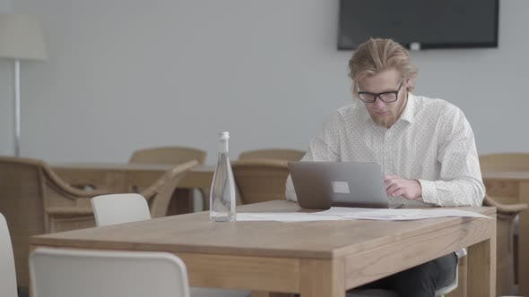 Thumbnail for Portrait Successful Blond Thoughtful Man in Glasses Sitting at the Table