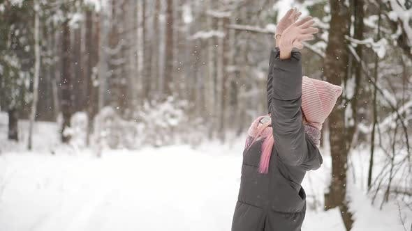 Thumbnail for Slow Motion, a Woman in a Jacket Hat and Scarf in the Winter in the Forest Holding Snow in Her Hands
