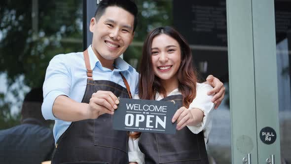 Business man and woman show open sign on front door smiling welcoming clients.