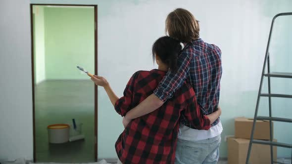 Thumbnail for Couple in Love Embrace Looking at Painted Wall