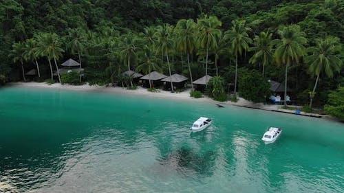 Boats Near Ocean Beach With Huts Among Palm Trees In Triton Bay, Raja Ampat.