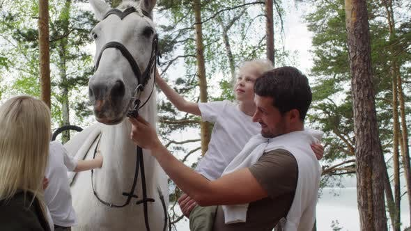 Family with Kids Petting White Horse