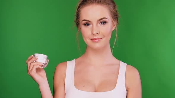 Thumbnail for Attractive Woman Applying Cream on Her Breast Isolated on Green