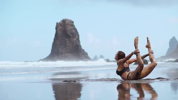 Thumbnail for A Beautiful Woman in a Swimsuit Performs an Exercise Bridge on the Beach with Black Volcanic Sand