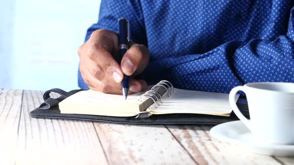 Thumbnail for Businessman Hand Writing with Pen on Notepad