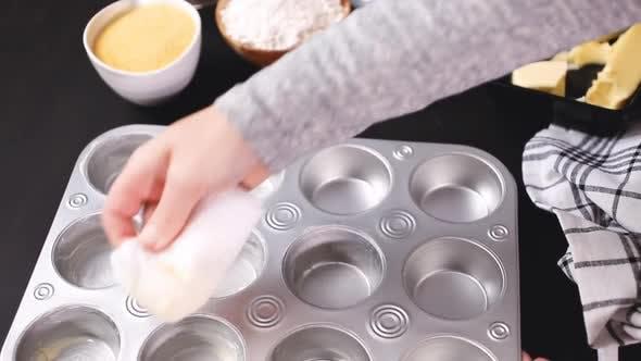 Schritt für Schritt. Buttering Metall Cupcake-Pfanne zum Backen von Maisbrot-Muffins.