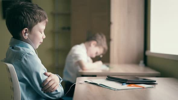 Children Do Their Homework One Sits at the Table with Notebooks